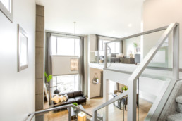 Homes for sale in Spruce Grove, this new showhome is bright and modern. Staircase showing down into nicely decorated living room.