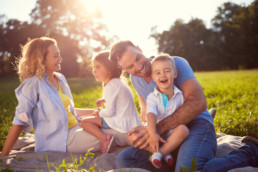 Family of four sit in sunny field in Dog Creek, in Spruce Grove. Residents of Jesperdale community raise their family in family-friendly neighbourhood.
